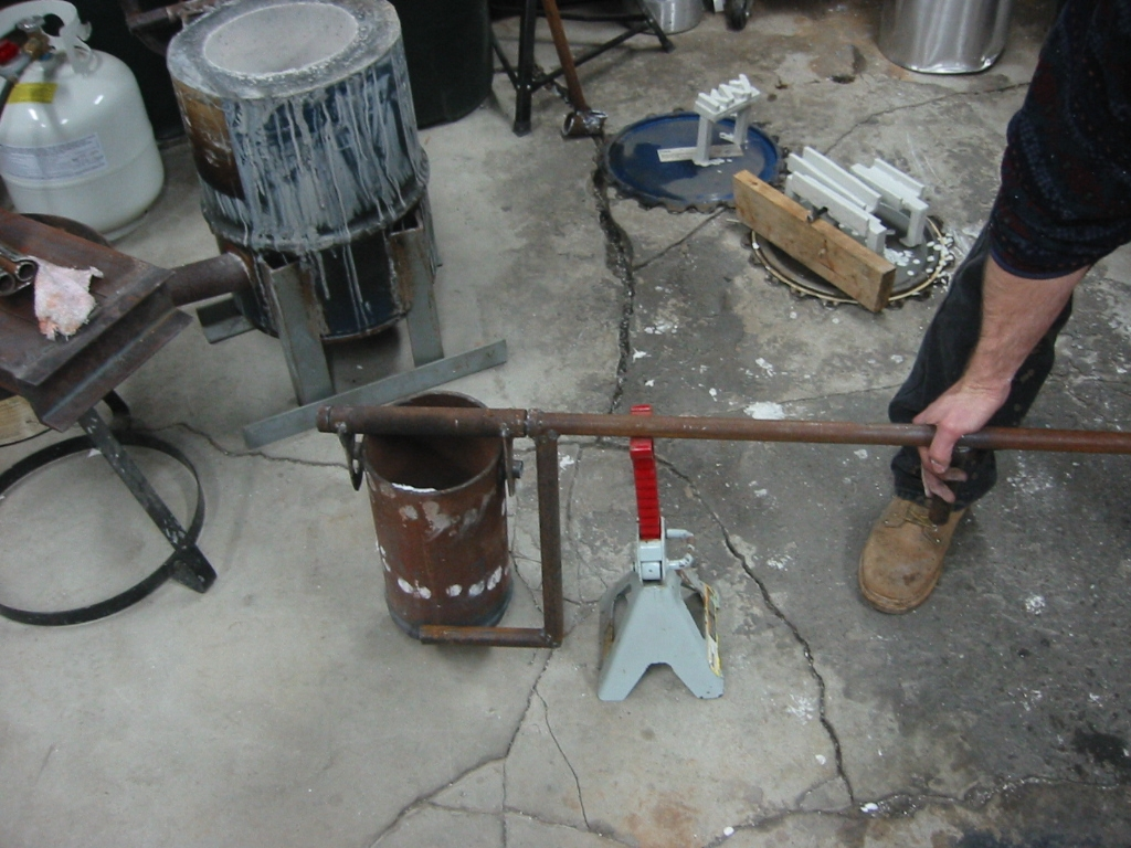 (15) Tilting arm that is welded to  the handle is rotated down to tilt the crucible for pouring.