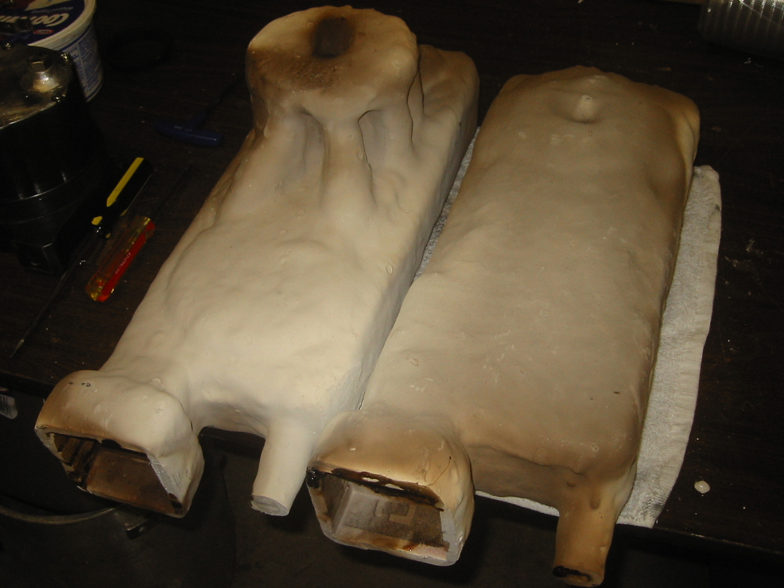 (7) Parts after they have be  fired in the foundry to harden the investment and burn off the  remains of the foam.