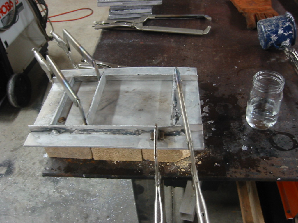 (1) Aluminum mold sitting on fire bricks and clamped down to the work table.