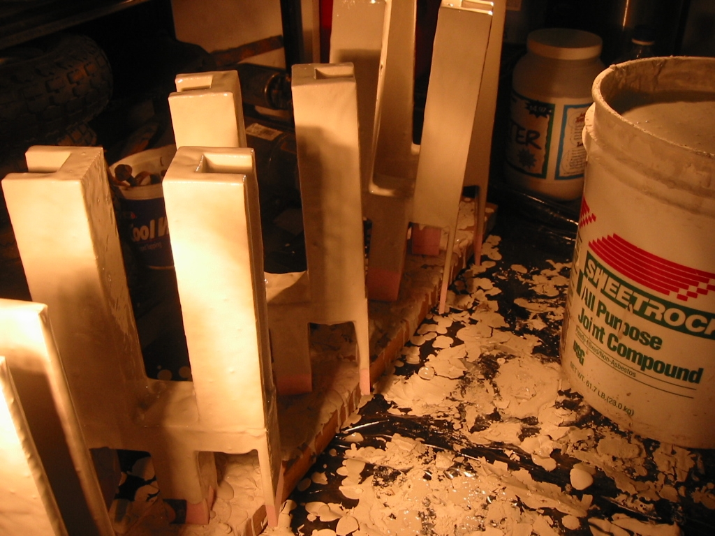 (2) Sheetrock mud coated parts drying in front of a heat lamp.  Others are drying in an oven at 175 degrees F.